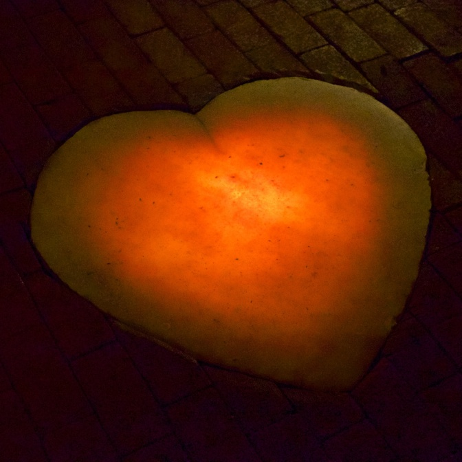 Heart made of calcite, lit from behind, on brick floor.