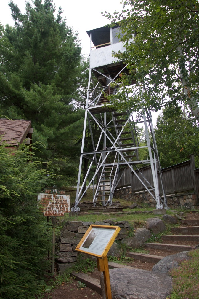 Fire Tower, in steel, with numerous signs in front of it.