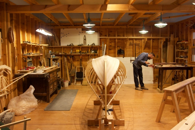 Boatbuilding workshop with worker in background.