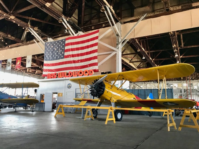 Interior of Naval Air Station hangar, with a yellow biplane in foreground and an American flag hanging from the ceiling.
