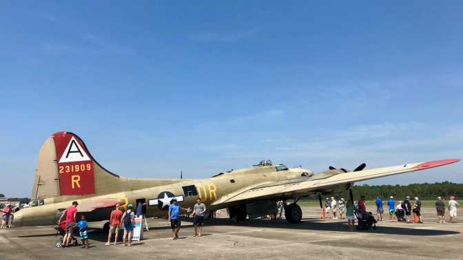 B-17 Flying Fortress bomber parked on tarmac, with people walking around it.