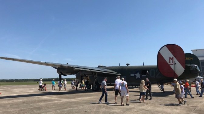 B-24 Liberator parked on tarmac with people milling around it.
