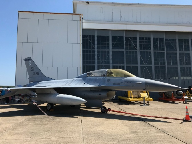 F-16 Falcon parked outside, beside hangar.
