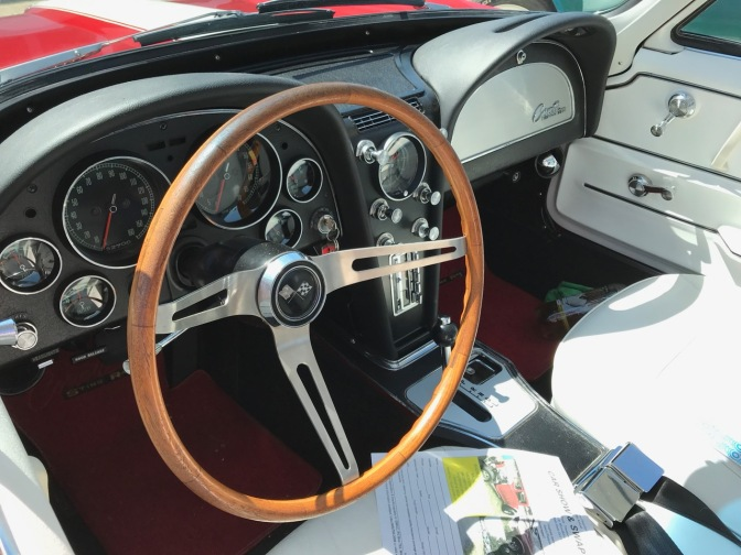 Interior of Corvette with black dashboard and white seats.