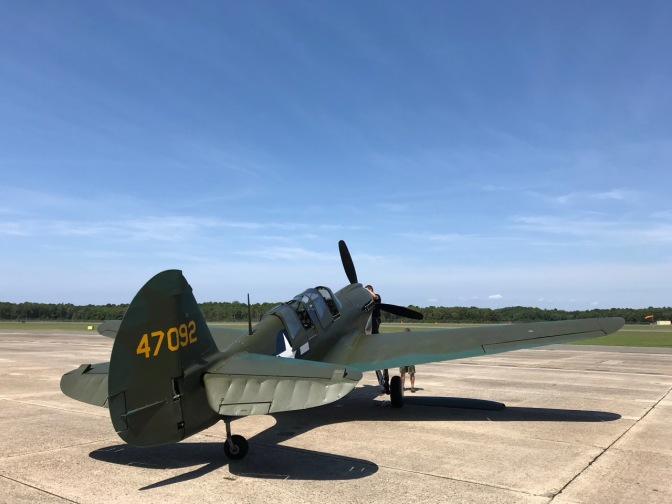 Curtiss P-40 Warhawk fighter on tarmac of museum.