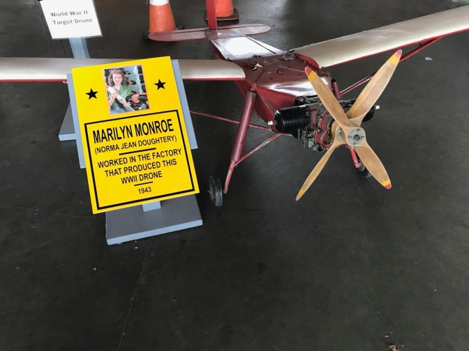 Small drone with sign that says MARILYN MONROE (NORMA JEAN DOUGHERTY) WORKED IN THE FACTORY THAT PRODUCED THIS WWII DRONE - 1943