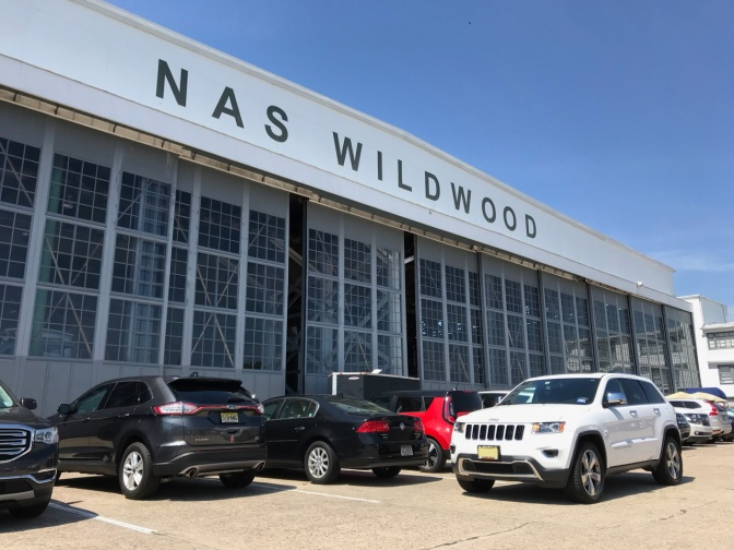 White Jeep Grand Cherokee parked in front of NAS Wildwood hangar.