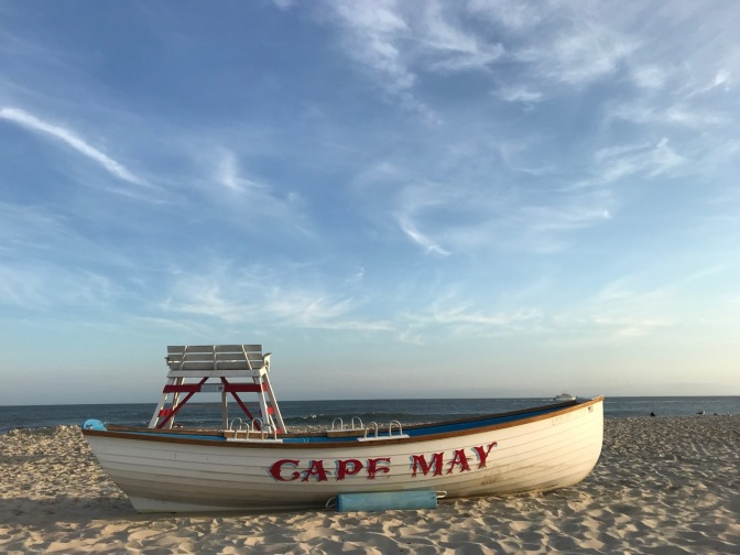 Seashore of Cape May, with lifeboat in foreground that says CAPE MAY. Lifeguard stand is behind it, and sea is in distance.