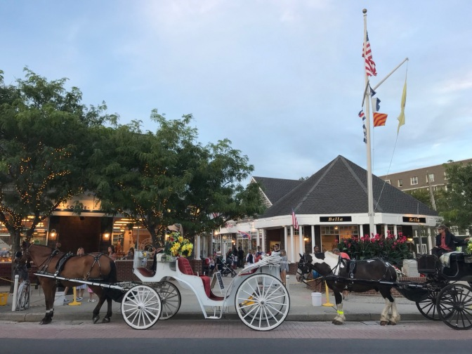 Two horse-drawn carriages in front of shopping plaza.