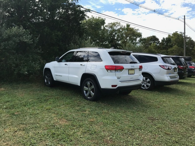 Jeep parked on field in row of cars and SUVS.