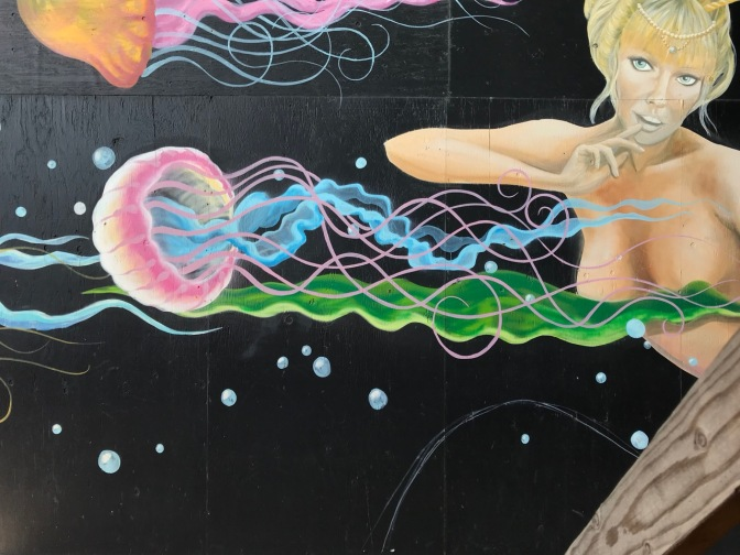 Mural of jellyfish swimming past mermaid.