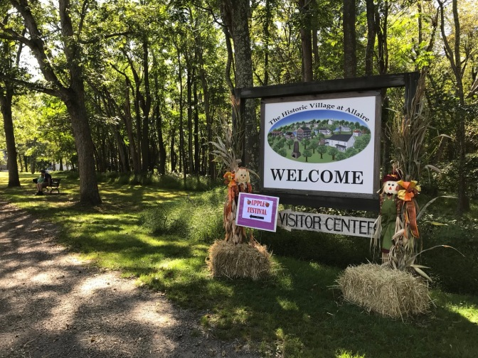 Entrance sign that says THE HISTORIC VILLAGE AT ALLAIRE WELCOME VISITOR CENTER, surrounded by straw bales and fall decorations.