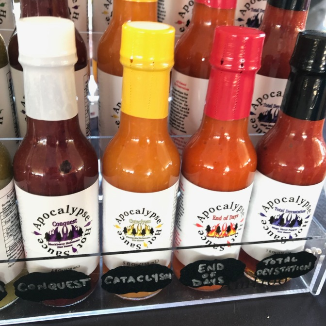 Hot sauce bottles, with signs that say CONQUEST, CATACLYSM, END OF DAYS, and TOTAL DEVASTATION.