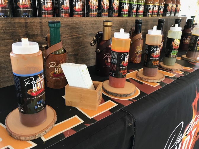 Row of hot sauce bottles to taste, with glass bottles of hot sauce in rows behind.