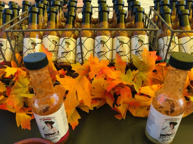 Bottles of hot sauce, with leaves on table behind them.