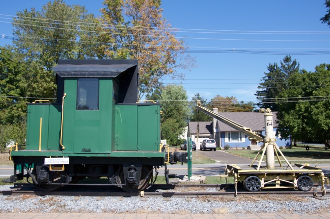 Locomotive on left and crane on right, both on railroad tracks.