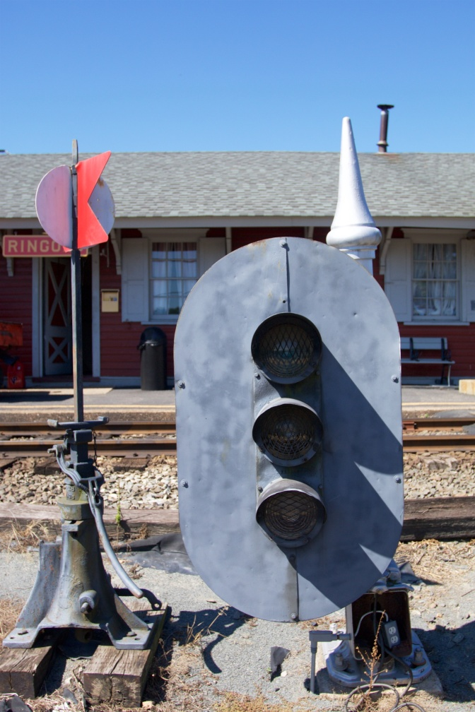 Train signal and stand in front of station.
