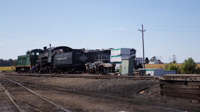 Train locomotives in train yard, being repaired.