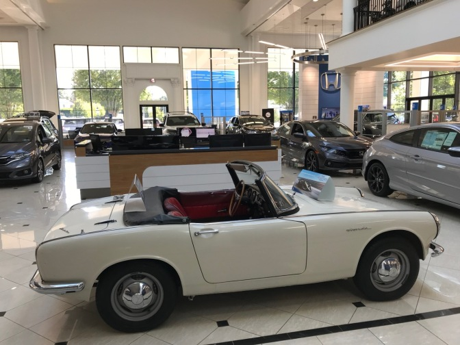 White Honda S800 convertible on showroom floor with newer Hondas in background.