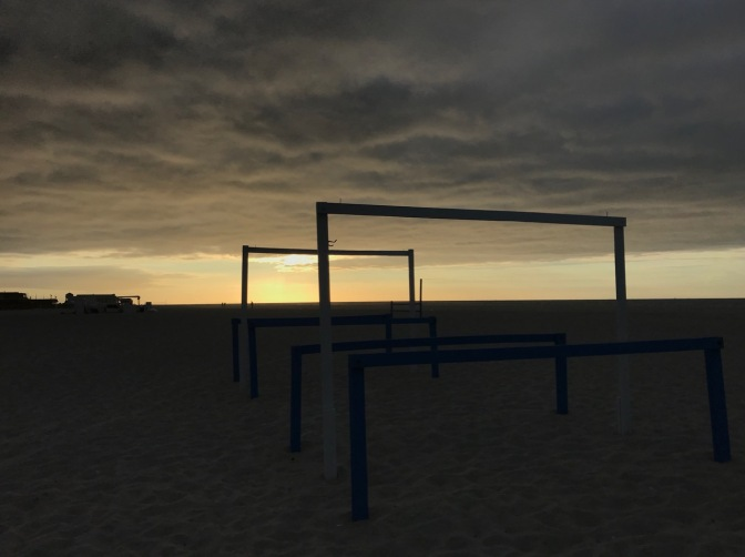 Tent frames on beach, with sunrise breaking through clouds.