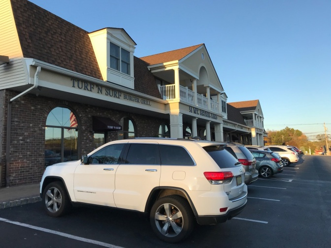 2014 Jeep Grand Cherokee parked in front of Turf N Surf Burger Grill.
