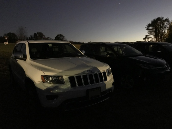 2014 Jeep Grand Cherokee parked in field at dusk.