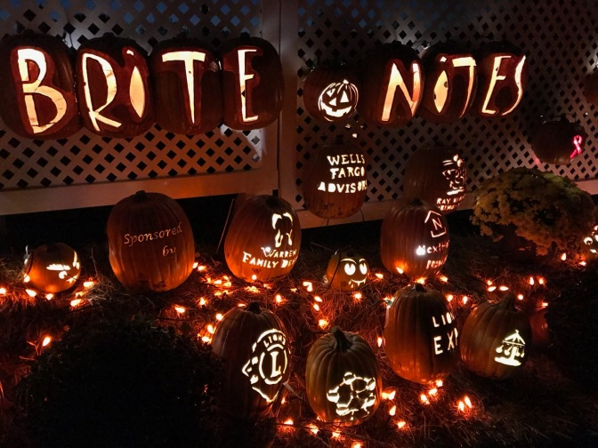 Stand of Pumpkins with sign carved into pumpkins saying BRITE NITES and logos for sponsors carved into other pumpkins.