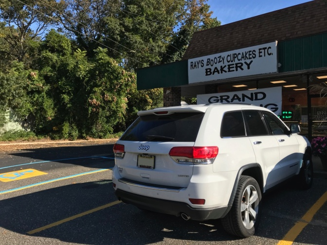 2014 Jeep Grand Cherokee parked in front of strip mall. Sign above door says RAY'S BOOZY CUPCAKES ETC. BAKERY.