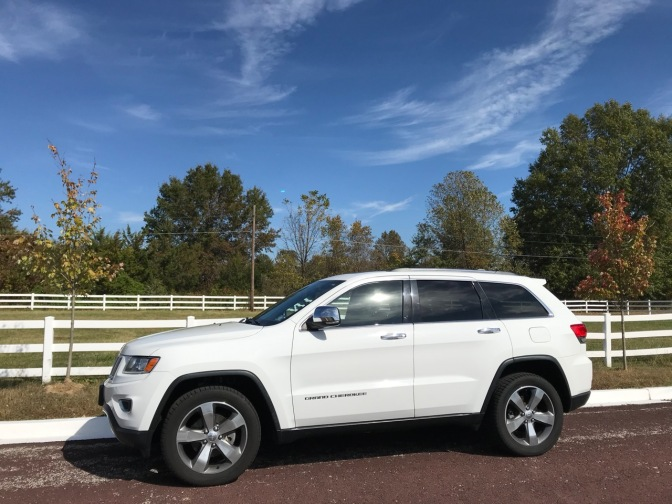 White 2014 Jeep Grand Cherokee, parked in front of a white picket fence.