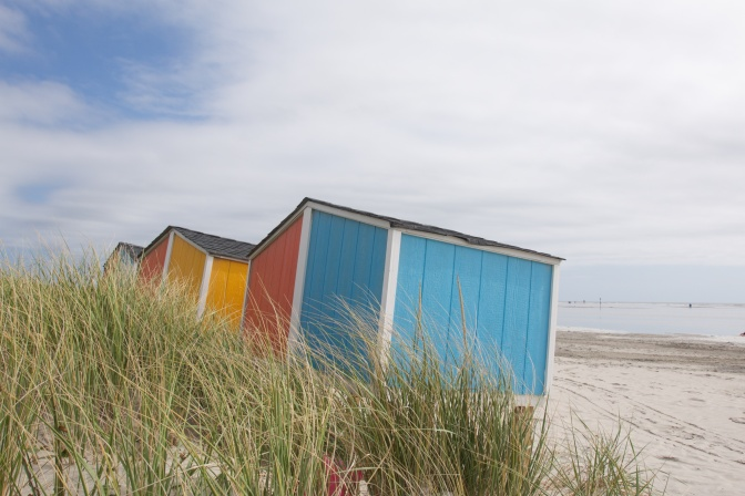 Blue, orange, and red storage huts on beach.