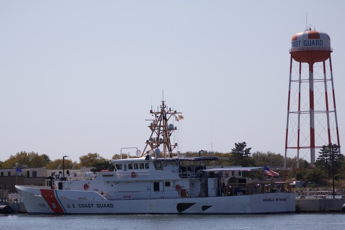 USCG cutter docked in front of Coast Guard water tower.