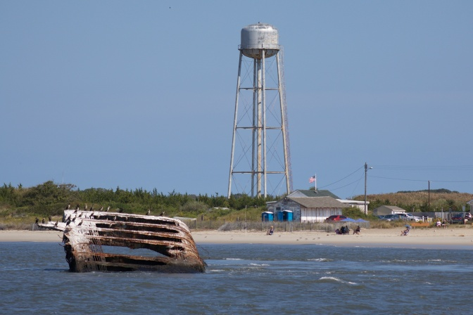 SS Atlantus wreckage in the ocean, with a water tower on the beach in the background.
