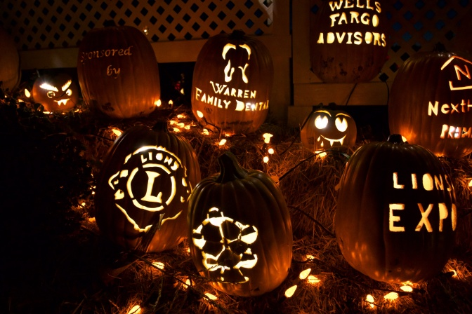 Logos of sponsors carved into pumpkins, including Lions Club, Warren Family Dental, Wells Fargo, and Lions Expo.