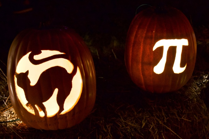 Two pumpkins one carved with a black cat, the other with the Pi symbol.
