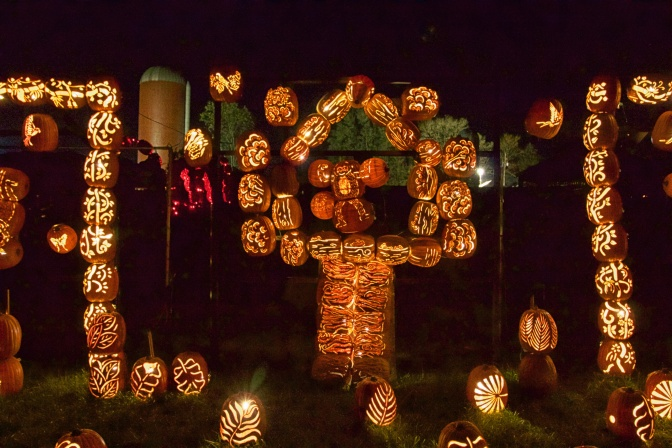 Monkey standing in a tree, all made of pumpkins.
