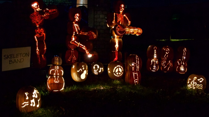 Skeletons playing instruments, carved out of pumpkins.