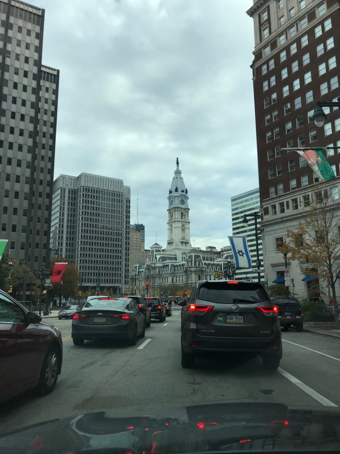 View of Philadelphia's City Hall beyond a line of traffic.
