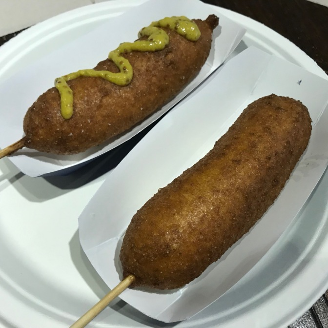 Two corn dogs, one with mustard, on a paper plate.