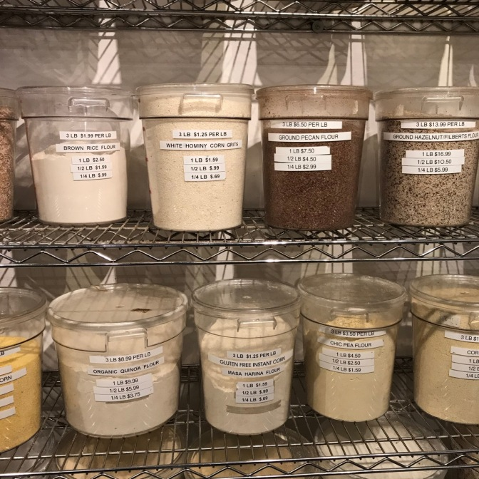 Plastic buckets of different flours and ground nuts.