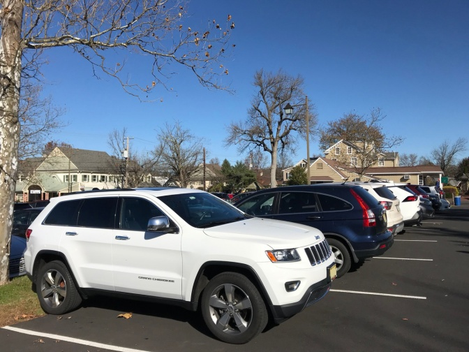 White Jeep Grand Cherokee at end spot in row in parking lot.