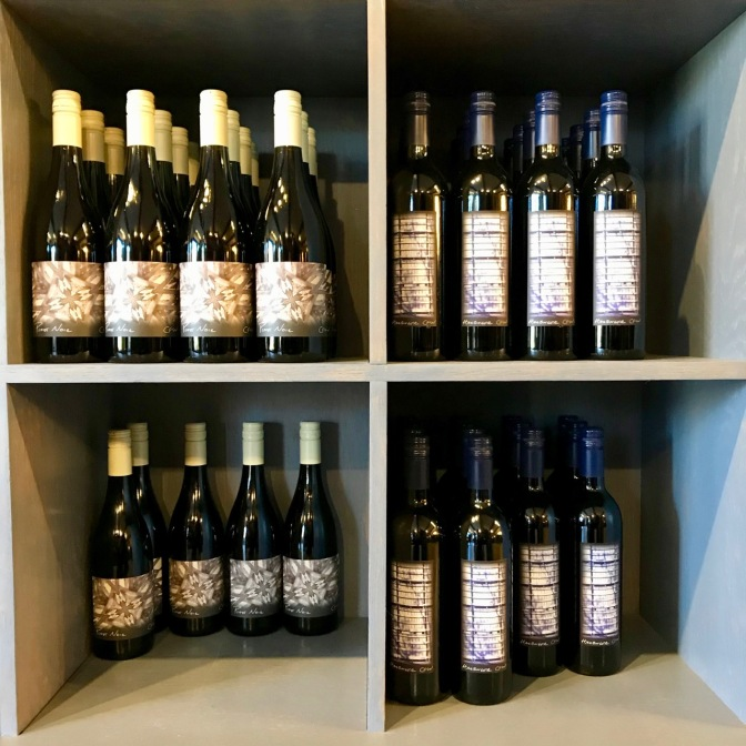 Wine bottles on shelves in four cubbyholes.