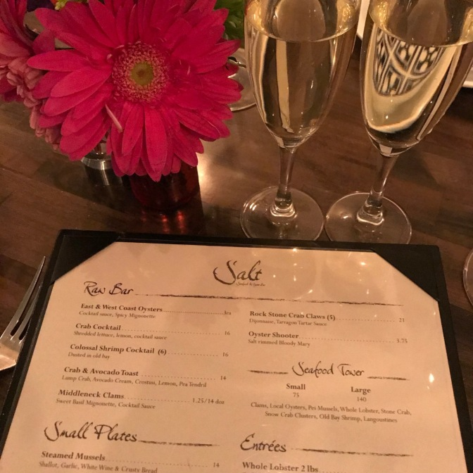 Two champagne glasses and menu at Salt restaurant.