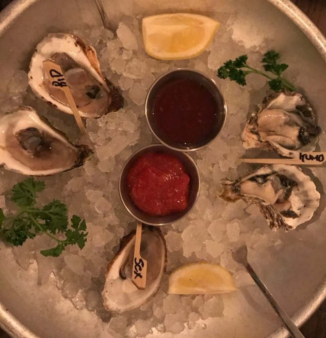 Steel bowl filled with ice and five oysters.