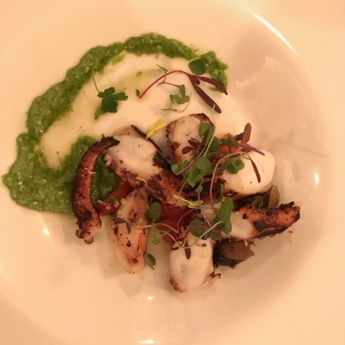Charred octopus with garlic scale pesto on a white plate.