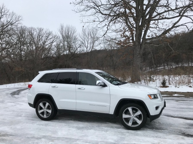 White Jeep Grand Cherokee parked on ice and snow-covered parking lot.