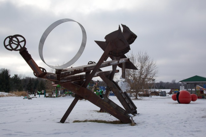Metal sculpture with elements including backhoe shovels and metal girders.