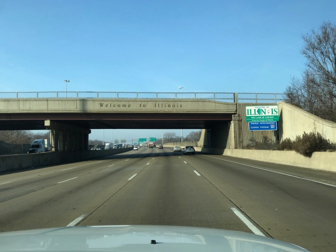 Blue-sky day with bridge that says WELCOME TO ILLINOIS over I-90.
