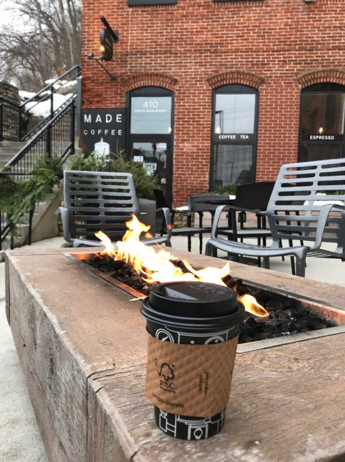 Cup of coffee on side of outdoor fire pit, with brick coffee shop in background.
