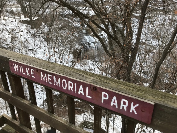 Sign on railing that says Wilkie Memorial Park overlooking a waterfall.