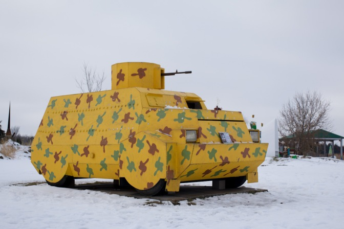 Sculpture of infantry fighting vehicle, covered in yellow with green camouflage.